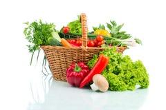 Sammansättning med rå grönsaker i vide- korg på whi Royaltyfri Foto