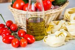 Sammansättning med rå pasta, grönsaker och olivolja Arkivbilder