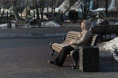 Sammanträde för äldre kvinna på träbänk i Catherine Park på en solig dag Arkivfoton