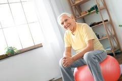 Sammanträde för övningen för den höga mannen vilar hemmastatt på övningsboll arkivfoto