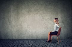 Sammanträde för affärskvinna på en stol framme av en vägg och tänka arkivfoto