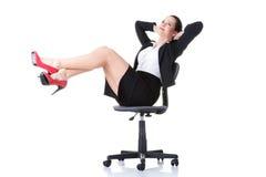 Sammanträde för affärskvinna på en stol med ben upp. Arkivfoton