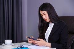 Sammanträde för affärskvinna på skrivbordet och användamobiltelefonen Arkivbilder
