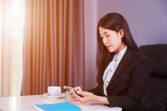 Sammanträde för affärskvinna på skrivbordet och användamobiltelefonen Royaltyfri Fotografi