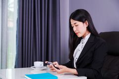 Sammanträde för affärskvinna på skrivbordet och användamobiltelefonen Arkivbild