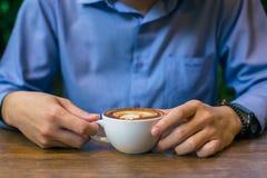 Sammanträde för affärsman och hållande kaffekopp royaltyfri bild