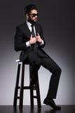 Sammanträde för affärsman på en stol, medan fixa hans omslag royaltyfria bilder