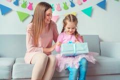 Sammanträde för beröm för moder och för dotter tillsammans hemmastatt på asken för gåva för soffaflickainnehav från mamma royaltyfria foton