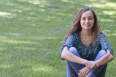 Sammanträde för den härliga unga kvinnan kors-lade benen på ryggen på gräset Royaltyfri Bild