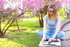 Sammanträde för den kvinnliga studenten med bärbara datorn, i att blomma, parkerar royaltyfri fotografi