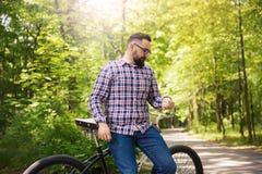 Sammanträde för den moderna mannen på cykeln på parkerar att tänka Fotografering för Bildbyråer
