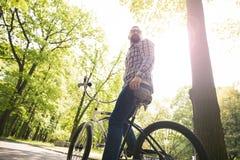 Sammanträde för den moderna mannen på cykeln som bort ser på, parkerar Fotografering för Bildbyråer