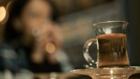 Sammanträde för den unga kvinnan i kafé utomhus, i hösten som slås in i en filt som, hon dricker te, tycker om aromen stock video