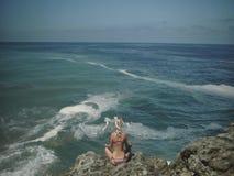 Sammanträde för den unga kvinnan i lotusblomma poserar och mediterar nära havet arkivfilmer