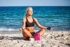 Sammanträde för den unga kvinnan i yoga poserar på stranden royaltyfria bilder