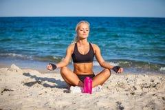 Sammanträde för den unga kvinnan i yoga poserar på stranden arkivfoto