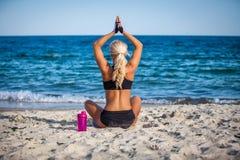 Sammanträde för den unga kvinnan i yoga poserar på stranden fotografering för bildbyråer