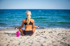Sammanträde för den unga kvinnan i yoga poserar på stranden royaltyfri bild
