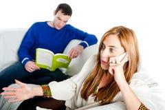 Sammanträde för den unga kvinnan på den hemmastadda soffan och att tala på en mobil stund hennes pojkvän läser Royaltyfri Bild