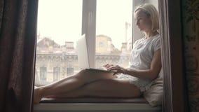 Sammanträde för den unga kvinnan på fönsterbrädan och använder en bärbar dator hemma stock video