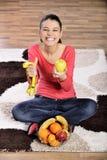 Sammanträde för den unga kvinnan på matta och att tycka om bär frukt royaltyfri bild