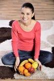 Sammanträde för den unga kvinnan på matta och att tycka om bär frukt royaltyfria bilder