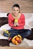 Sammanträde för den unga kvinnan på matta och att tycka om bär frukt Arkivfoton