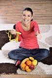 Sammanträde för den unga kvinnan på matta och att tycka om bär frukt royaltyfri foto