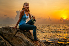 Sammanträde för den unga kvinnan på vaggar, genom havet och att hålla ögonen på soluppgången på en tropisk ö Fotografering för Bildbyråer