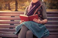 Sammanträde för den unga kvinnan parkerar på bänken med boken Fotografering för Bildbyråer