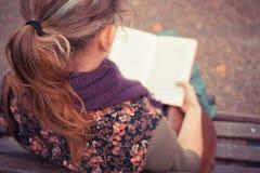 Sammanträde för den unga kvinnan parkerar på bänken med boken Arkivfoton
