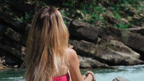 Sammanträde för den unga kvinnan vaggar på på banken av en bergflod i Schweiz tar av hans hatt och fördelar hans långa hår lager videofilmer