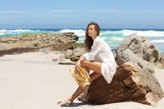 Sammanträde för den unga kvinnan vaggar på på stranden Royaltyfri Fotografi