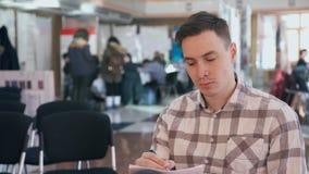 Sammanträde för den unga mannen i ett offentligt ställe och danande ritar handstil på papper stock video