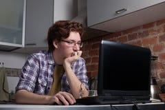 Sammanträde för den unga mannen på en bärbar dator och tänker om problemlösning royaltyfria foton