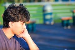Sammanträde för den unga mannen på parkerar, djupt i tanke Royaltyfria Bilder