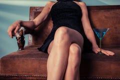 Sammanträde för elegant kvinna på soffan med coctailen arkivfoto