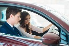 Sammanträde för försäljningschef i en ny bil med en härlig kund arkivfoton
