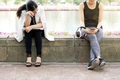 Sammanträde för formen för affärskvinnan parkerar tröttat hårt funktionsdugligt nära den avslappnande sportkvinnan i stad royaltyfria foton