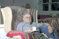 Sammanträde för hög man på soffan med koppen Royaltyfri Bild