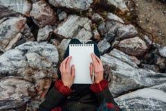 Sammanträde för konstnärflickamålning på vaggar på klippan, notepad Underbar nedgångsikt arkivbild