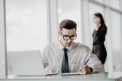 Sammanträde för kontorsarbetare på skrivbordet i regeringsställning som använder bärbara datorn, medan kvinnor som talar telefone royaltyfria bilder