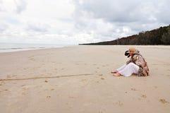 Sammanträde för kvinna och för älsklings- hund på den härliga öde stranden arkivfoto