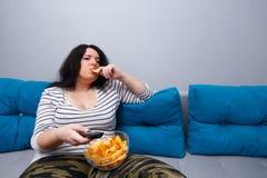 Sammanträde för kvinnan för soffapotatisen gå i flisor överviktigt på soffan som äter arkivbild