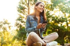 Sammanträde för kvinnastudent i parkera genom att använda lyssnande musik för mobiltelefon fotografering för bildbyråer