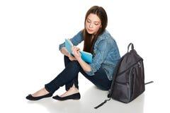 Sammanträde för kvinnlig student på golv med ryggsäcken som läser en bok Arkivfoton