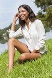 Sammanträde för Latina kvinnaflicka på gräs vid sjön i sommar Royaltyfri Fotografi