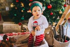 Sammanträde för litet barn på golvet nära julgranen Royaltyfri Bild