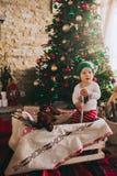 Sammanträde för litet barn på golvet nära julgranen Arkivbild