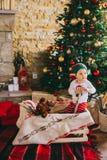 Sammanträde för litet barn på golvet nära julgranen Arkivbilder